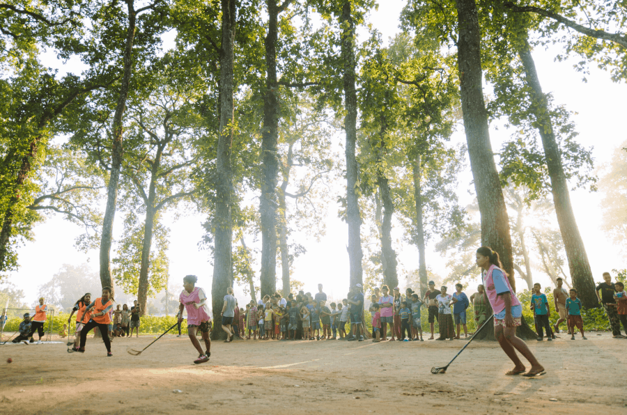 Children of the Himalayan Life Chitwan outreach hockey program play on a dirt field in the jungle of Southern Nepal